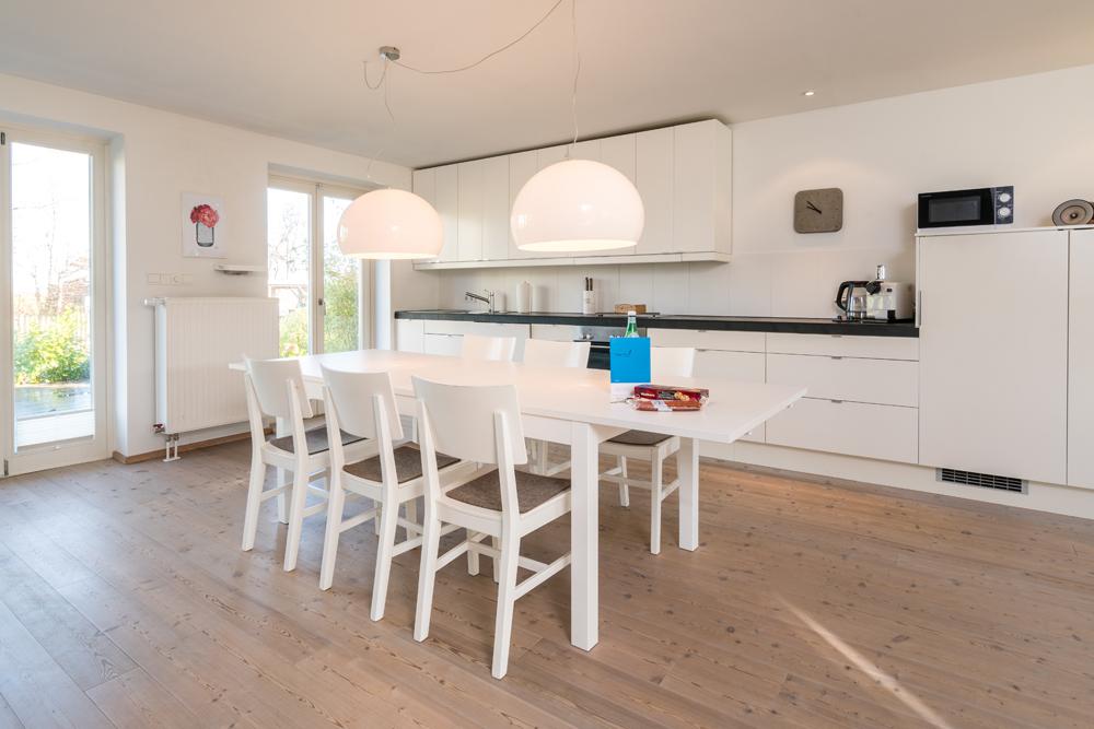 Esstisch mit Küchenzeile und Blick in den Garten und auf die Terasse
