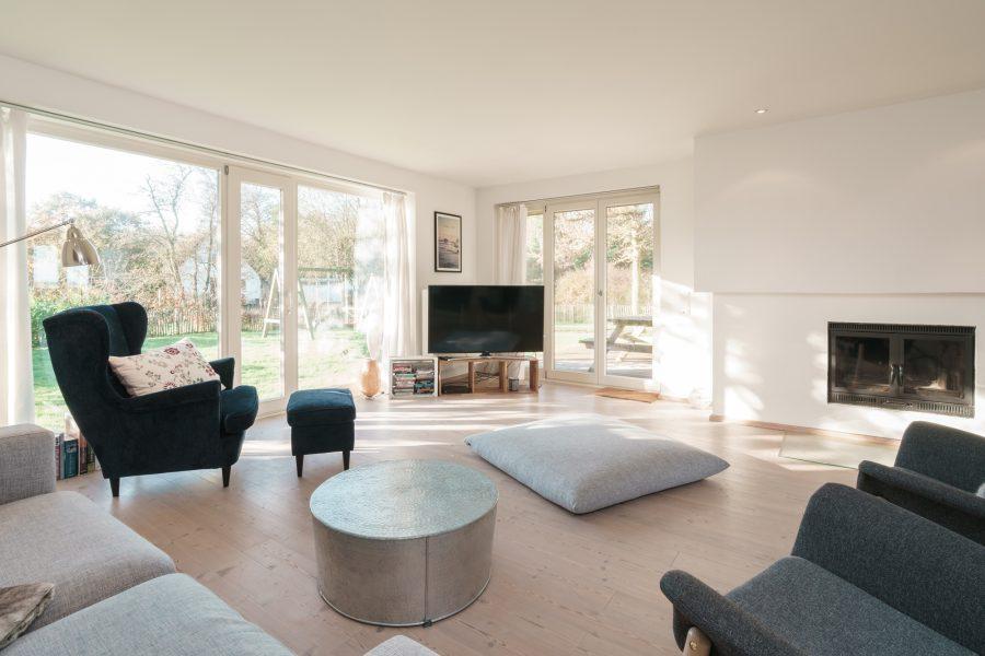 Wohnzimmer mit TV, Sitzgelegenheiten und Kamin